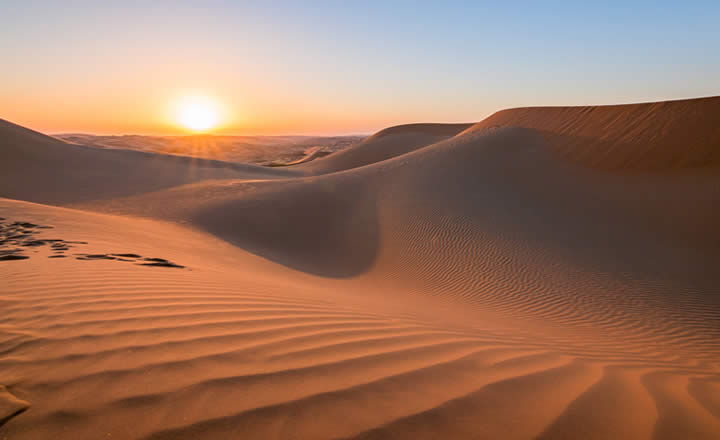 Dubai desert sand dunes and sunset