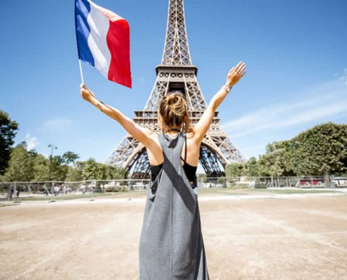 Female tourist holding French flag in front of Eiffel Tower