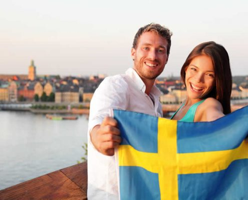 Tourists in Stockholm holding Swedish flag